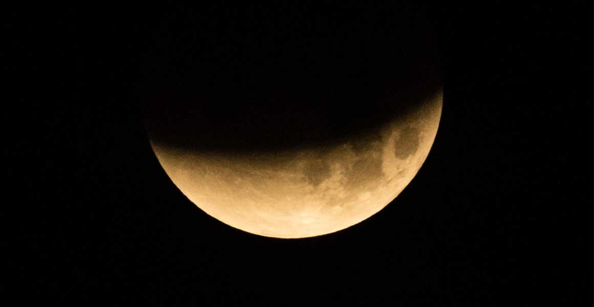 A NASA image of the moon in shadow. It is a yellow-orange colour - hence the name blood moon.
