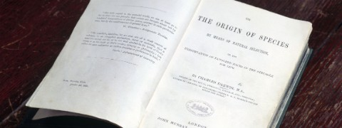 A first-edition copy of Charles Darwin's On the Origin of Species opened on the title page.