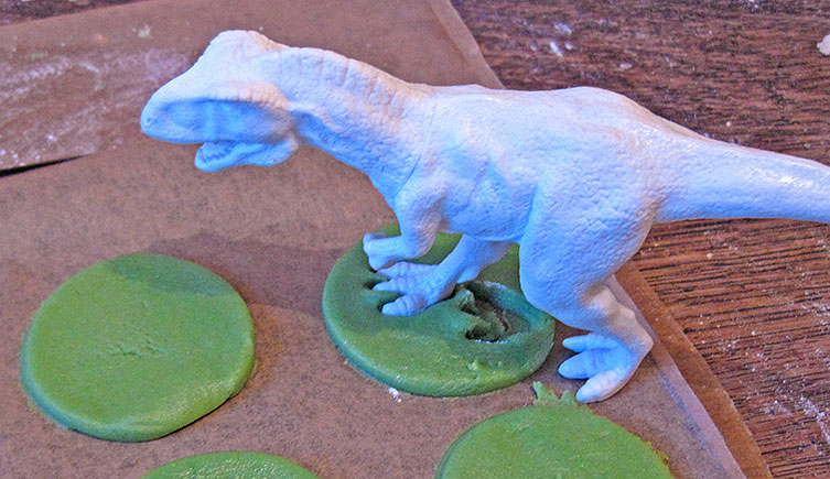Pressing a model dinosaur's foot into the dough