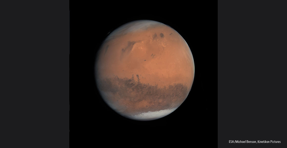 A full image of Mars, with white polar ice caps at the top and bottom.