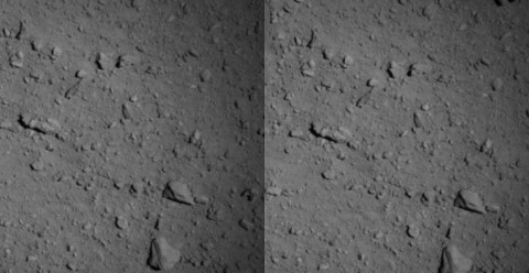 A grey image showing rocks and boulders on the asteroid's surface.