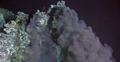 A hydrothermal vent chimney releasing black smoke