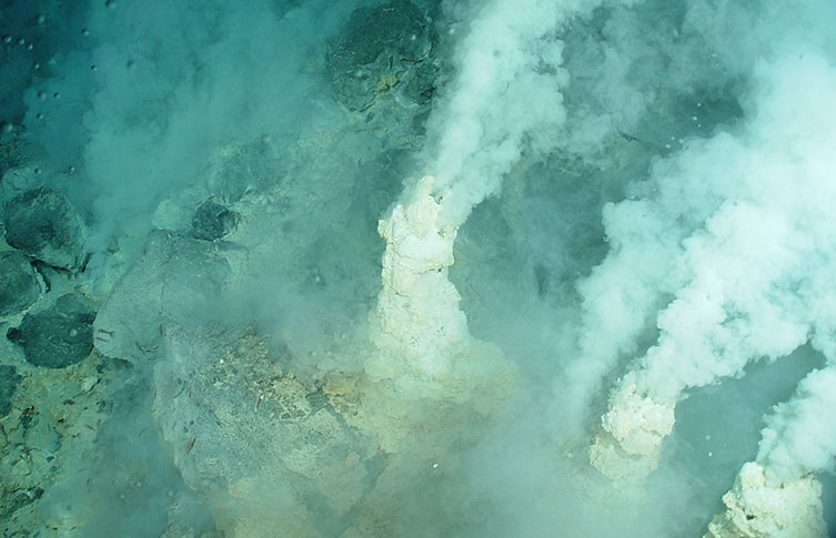 A hydrothermal vent chimney releasing white smoke