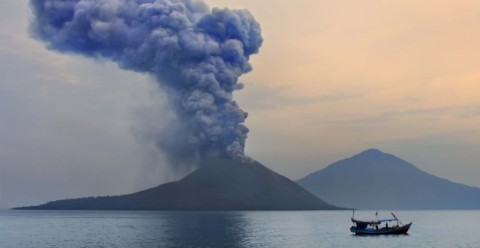 A boat glides over the water as Anak Krakatau erupts