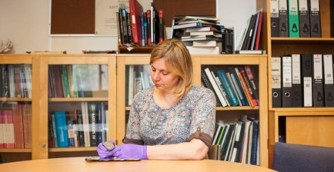 Sara Russell observes a moon rock in her office