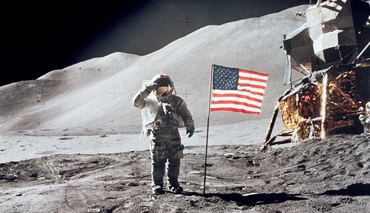 Astronauta saludando a la bandera de Estados Unidos en la Luna