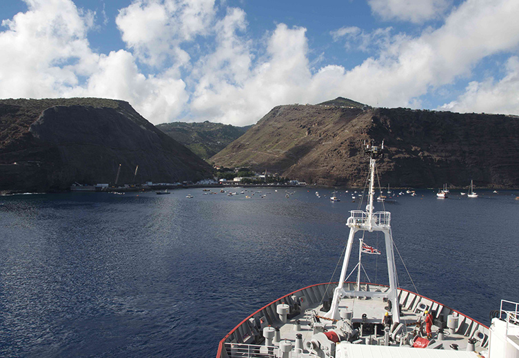 An image taken from the top of a the RRS James Clark Ross, showing the front of the ship heading towards the edge of St Helena island.