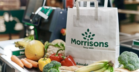 A paper bag among fruit and vegetables on a supermarket conveyor belt