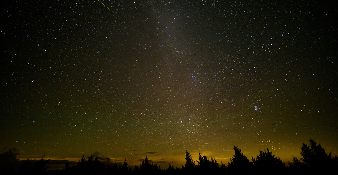 In this 30 second exposure, a meteor streaks across the sky during the annual Perseid meteor shower