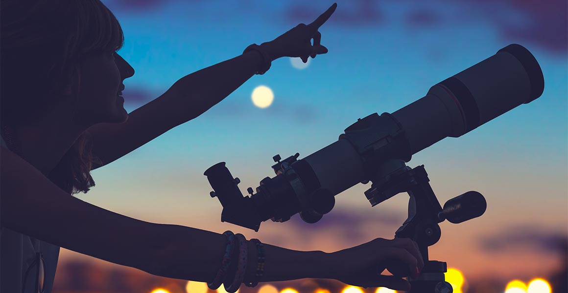 A silouette of a woman looking through a telescope, with city lights in the background.
