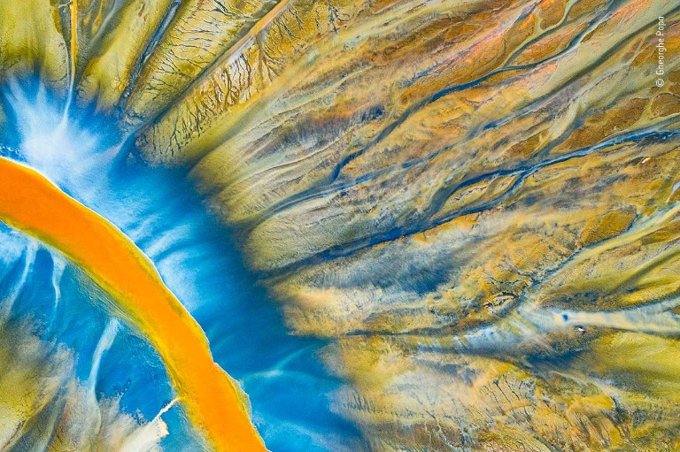 A bright orange river curves through a colourful landscape