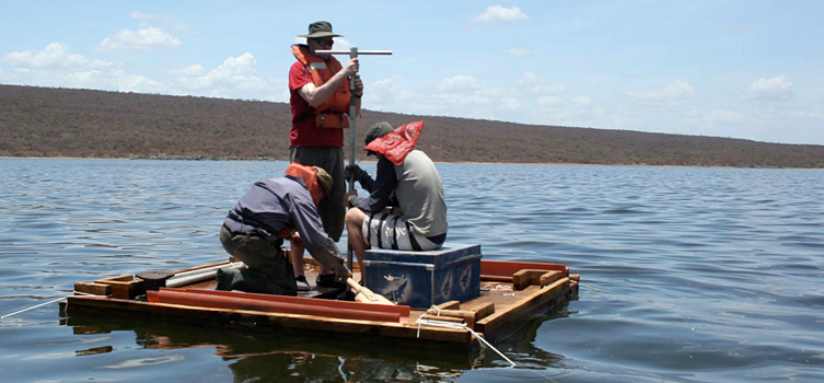 A scientific team collecting lake sediment samples.