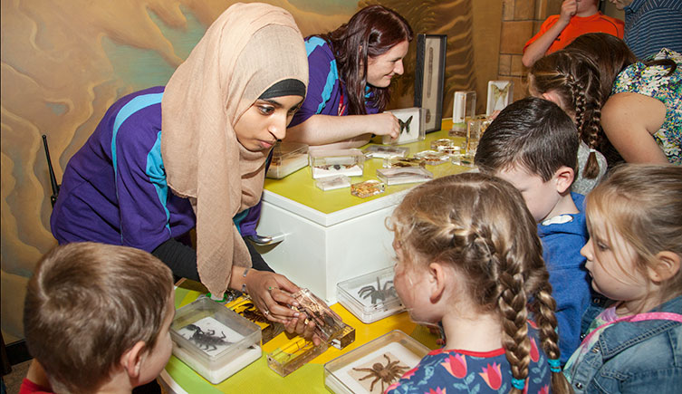 Two volunteers showing specimens to children