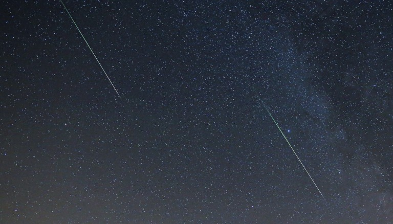 The night sky, with two meteors pictured as bright flashes.