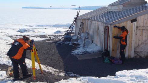 Members of the Antarctic Heritage Trust surveying the hut at Cape Evans