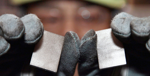 An employee at a machinery plant in Japan shows rare earth magnets.