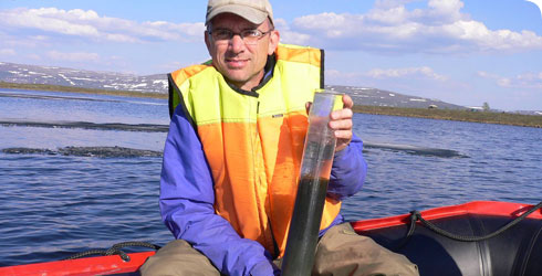 Steve Brooks displaying a mud core on a boat