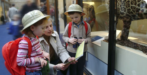 A family with an Explorer backback, enjoying the Mammals gallery