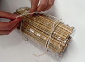 Tying a bow around the packed tube to build a bee hotel