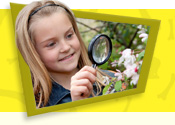 Girl looking at a plant close-up with a magnifying glass