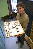 Laurence Livermore holding a museum drawer containing large coreid bugs.