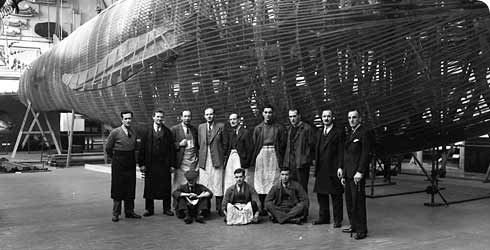 Staff posing with blue whale model, 1938.