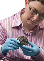 Dr Caroline Smith, meteorite expert, holds the Ivuna meteorite.