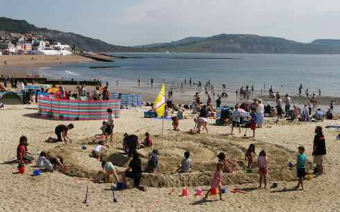 Children build a giant sand ammonite at the Lyme Regis Fossil Festival