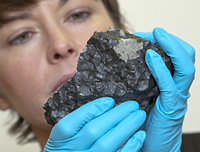 Museum scientist Dr Caroline Smith holds the newly arrived Tissint Martian meteorite
