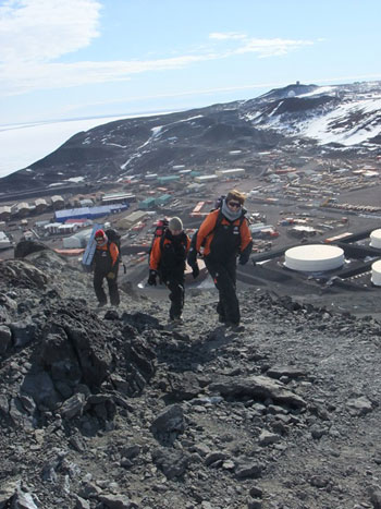 Climbing up Observation Hill wtih McMurdo Station in the background © Antarctic Heritage Trust / J Hamill