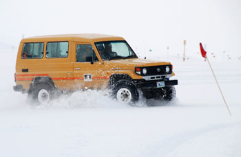 Nicola driving the vehicle through a snow drift © Antarctica New Zealand, Steven Sun