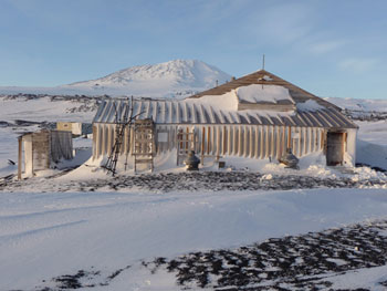 Captain Scott's 1910 base at Cape Evans with Mount Erebus in the background © Antarctic Heritage Trust