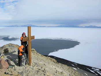 Examining the Observation Hill Cross with a view of McMurdo Sound © Antarctic Heritage Trust / N Dunn