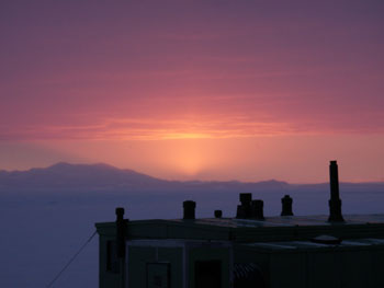 The sun sets over New Zealand's Trans-Antarctic Expedition Hut c. 1957 at Scott Base © Antarctic Heritage Trust / M Bell
