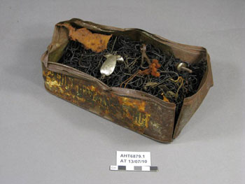 Tin of fish hooks, after treatment, with silver-coloured fish-shaped lure sitting on top © AHT / M Bell