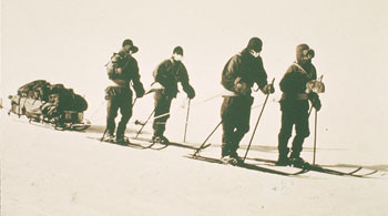 Scott's southern party hauling a sledge with harnesses, photographed by Herbert Ponting