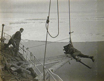 Photographer and camera artist Herbert Ponting hanging off the side of the ship trying to get the perfect shot © Canterbury Museum