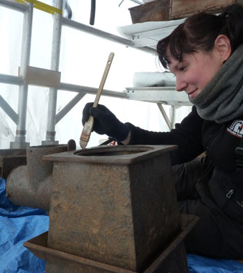 Up close and personal - Fran working on the stove © Antarctic Heritage Trust